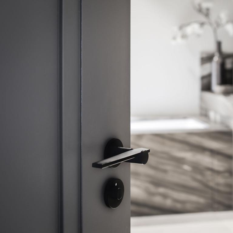 Satin black door handle on rose