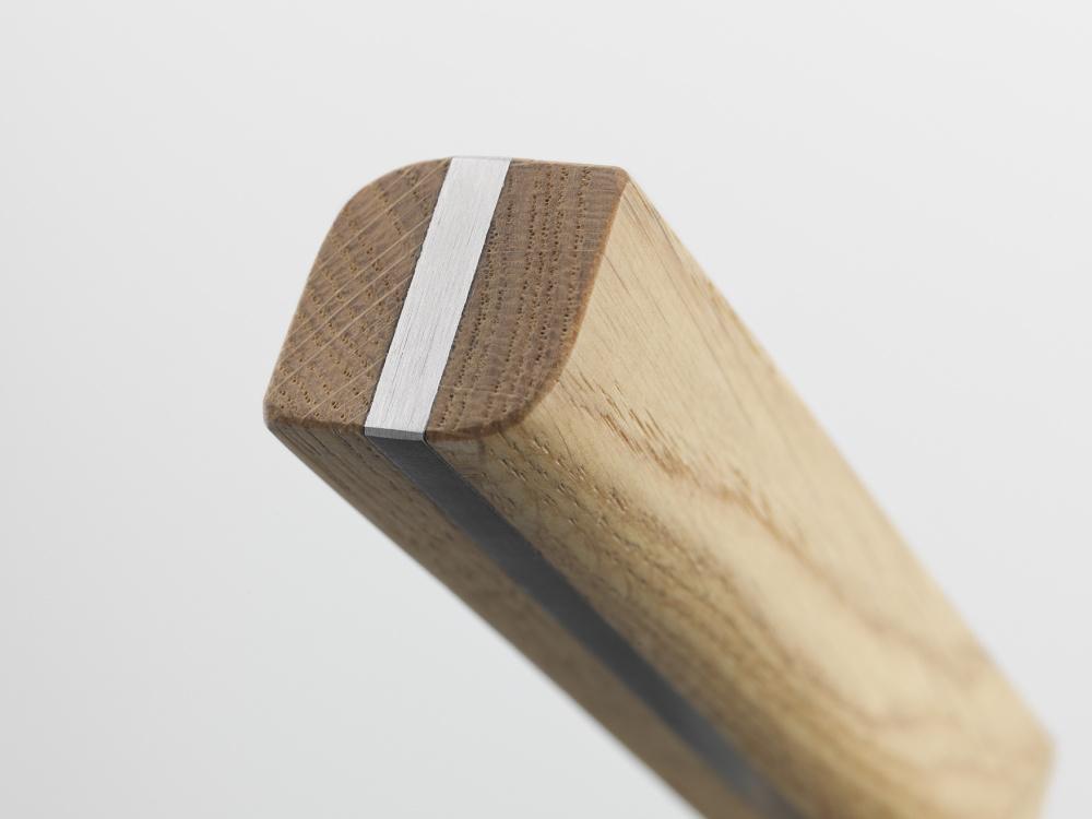 Satin stainless steel door handle on oak wood